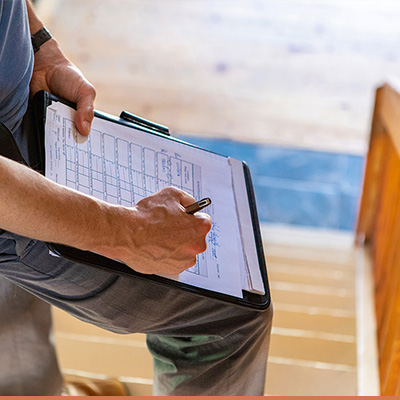 Home inspector with clipboard on staircase