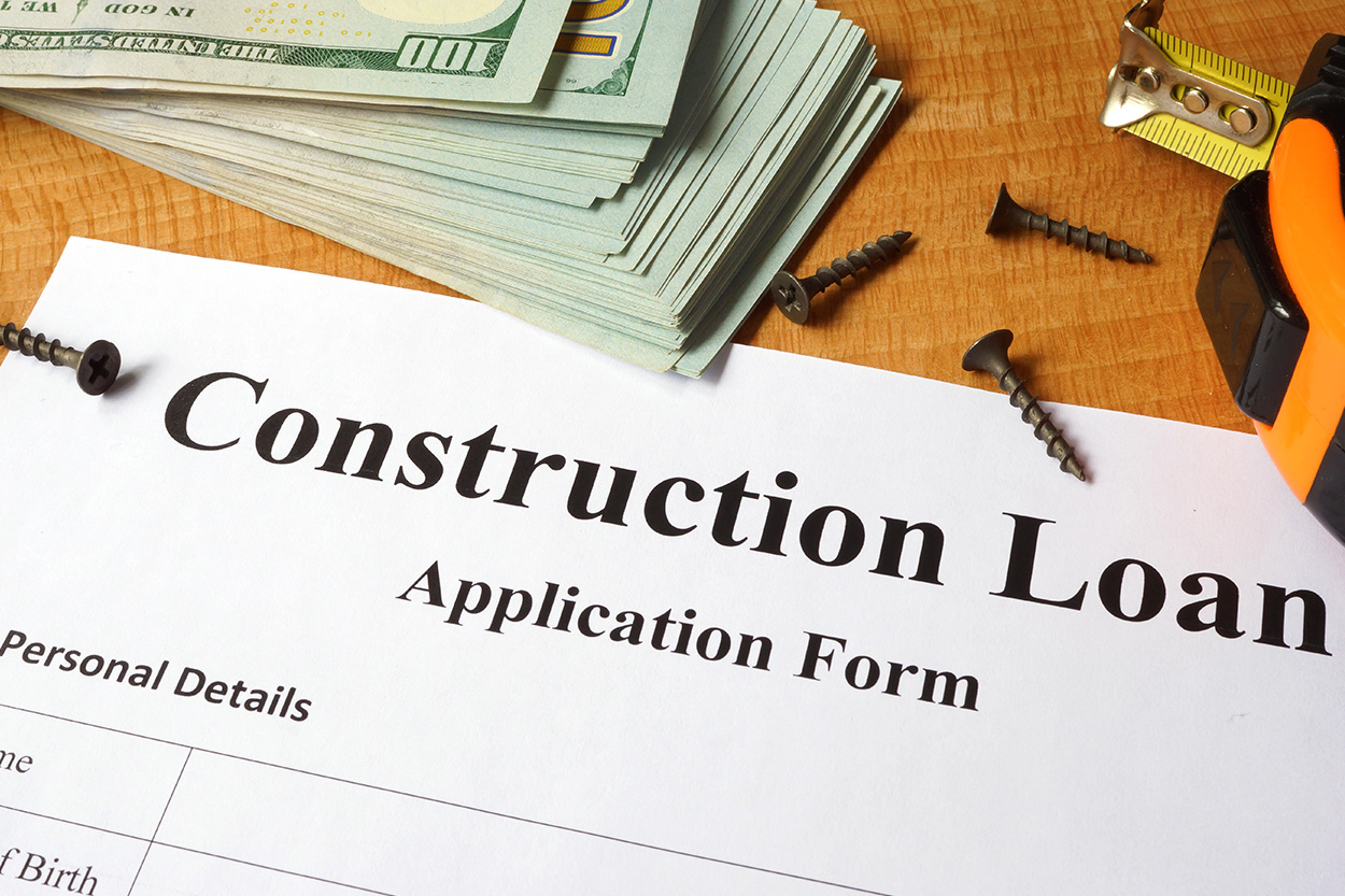 paperwork for construction loan with cash and nails on counter