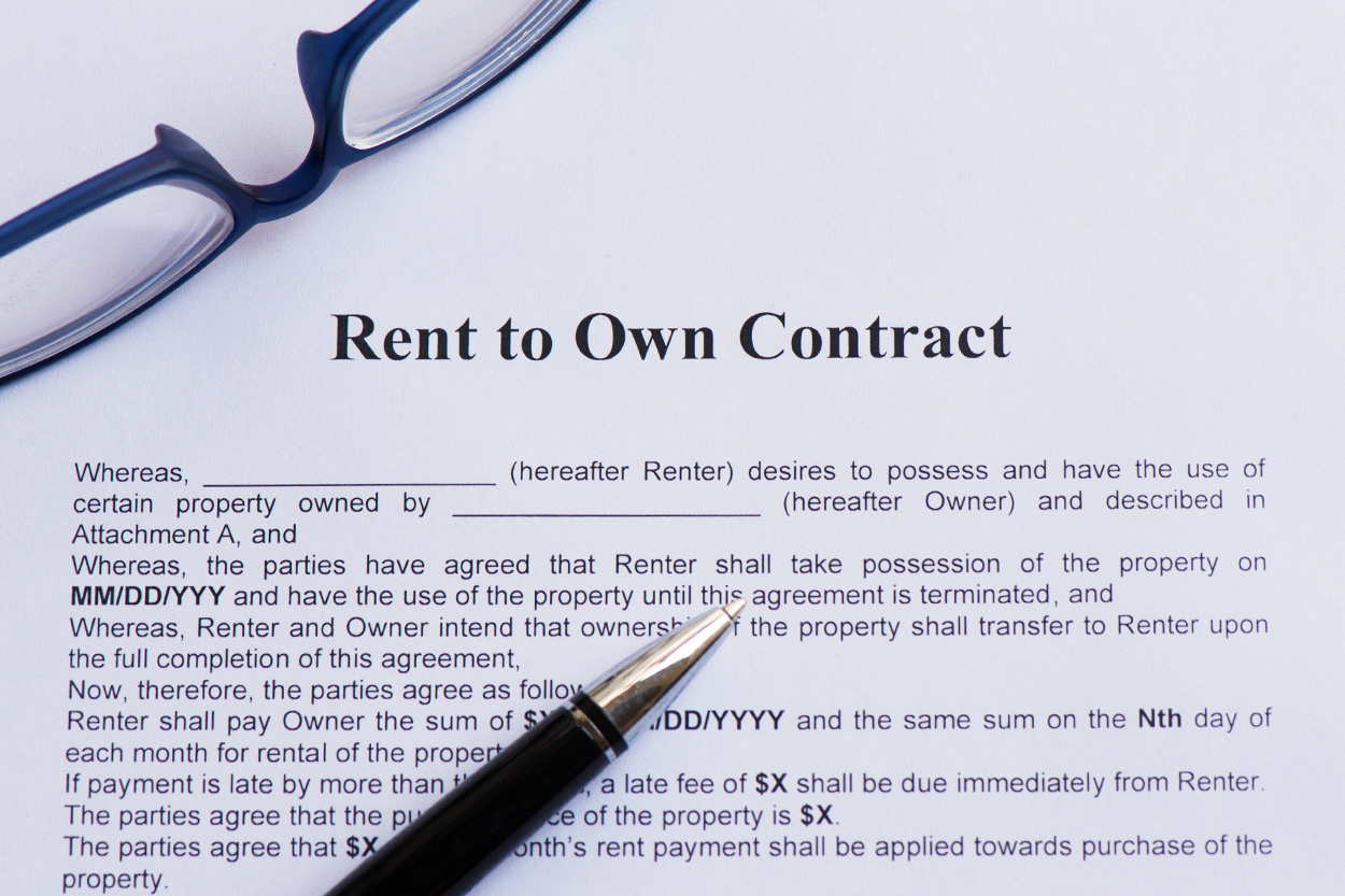 Rent to own contract paperwork with pen and glasses