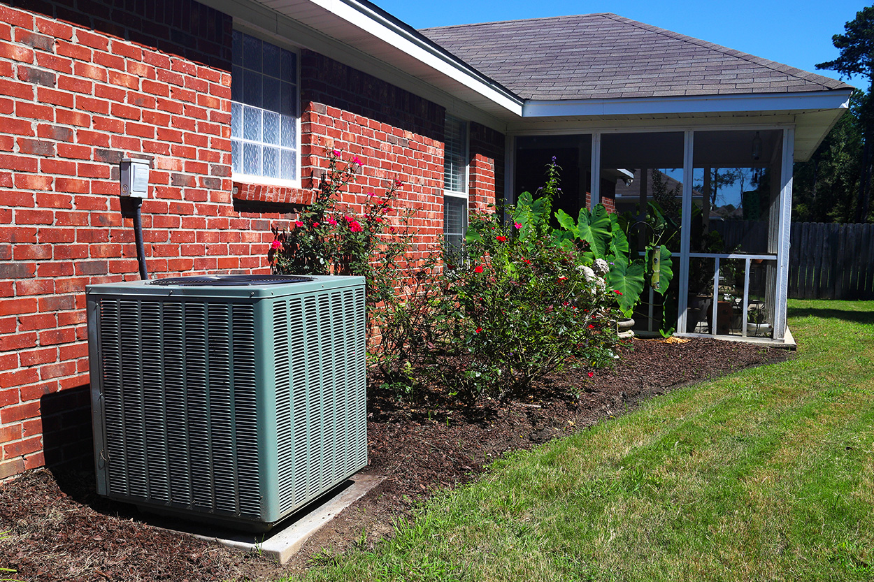 Central Air Conditioning unit outside brick house with porch