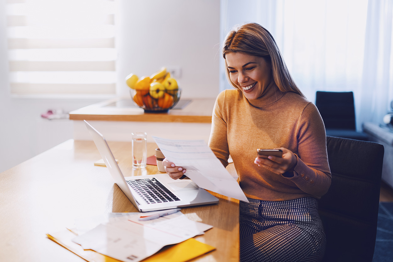Young woman reviewing paperwork at home smiling