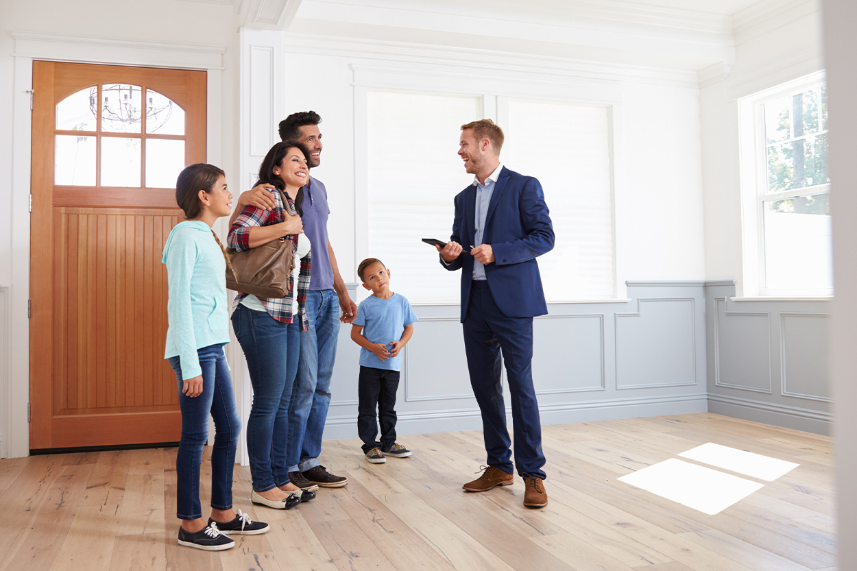 Family touring an empty home with realtor