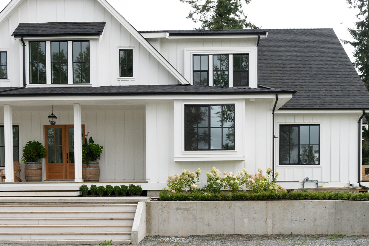 Exterior of new house with black trim and white siding
