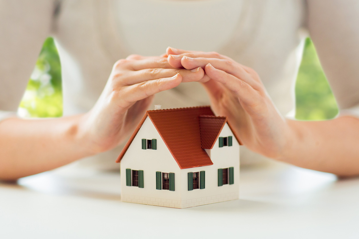 Woman covering house with hands
