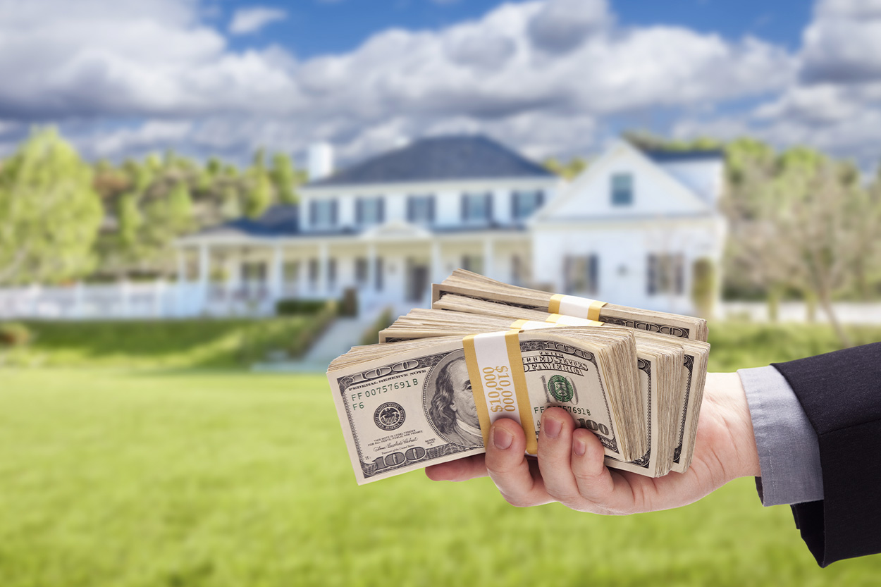 Man holding cash down payment with house in background